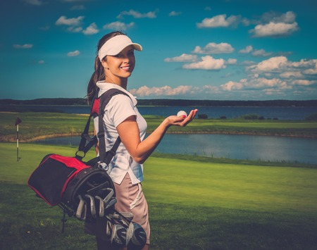 putter: Young cheerful woman with bag and ball on a golf field