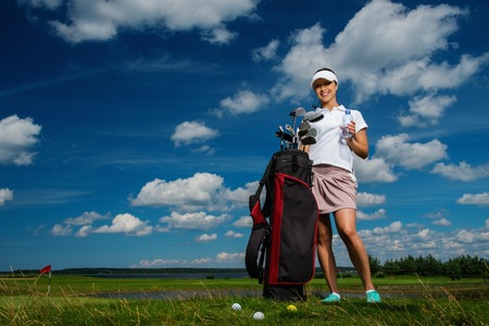 Young cheerful woman with bag and bottle of water on a golf field photo