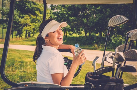 water hole: Young cheerful woman with bottle of water driving golf cart