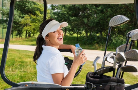 golfing: Young cheerful woman with bottle of water driving golf cart