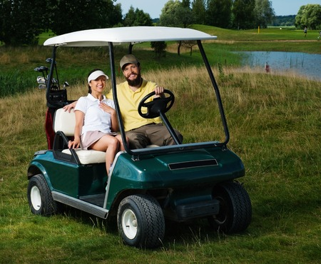 Happy couple driving golf cart  photo