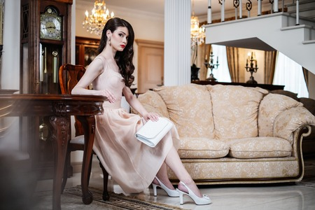 vintage chair: Beautiful young woman in luxury house interior  Stock Photo