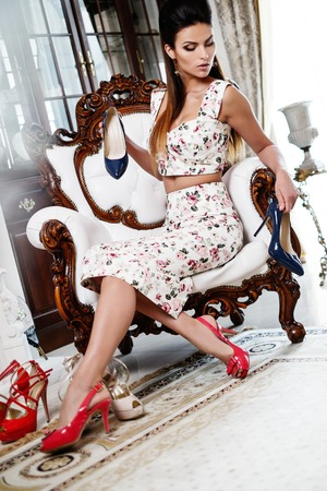 high chair: Beautiful woman choosing shoes in luxury home interior  Stock Photo