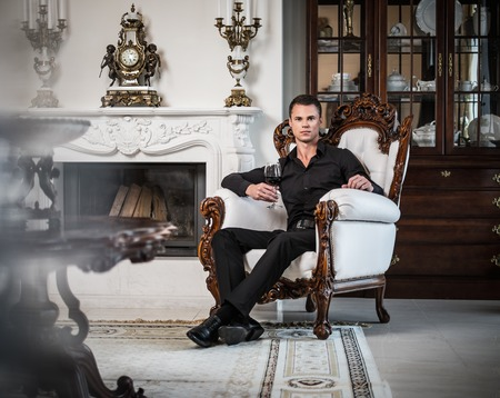 man in chair: Handsome well-dressed man sitting with red wine in luxury  house interior