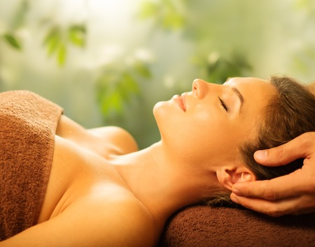 Young woman having face massage in a spa salon photo
