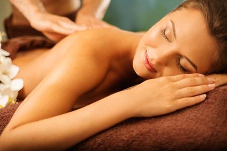 Hermosa mujer joven que tiene masaje en un salón de spa