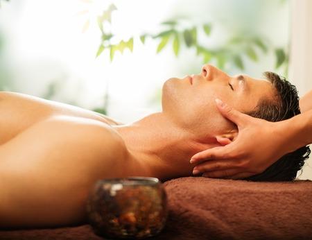 massage homme: Bel homme ayant massage du visage dans le spa salon
