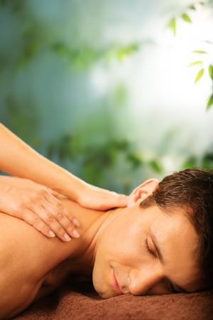 facial massage: Handsome man having massage in spa salon Stock Photo
