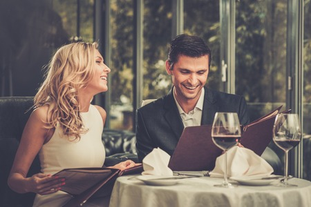 dating: Cheerful couple with menu in a restaurant