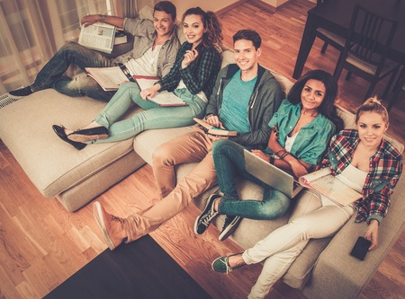 Group of multi ethnic young students preparing for exams in home interior  photo