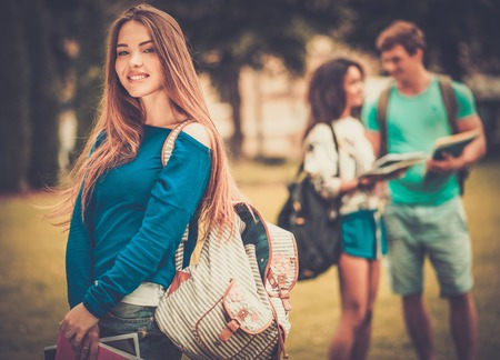 Beautiful young girl student in a city park on summer day  photo