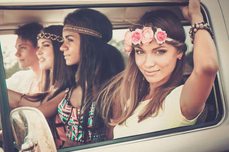 niña: Amigos hippie multi-étnicas en una camioneta en un viaje por carretera