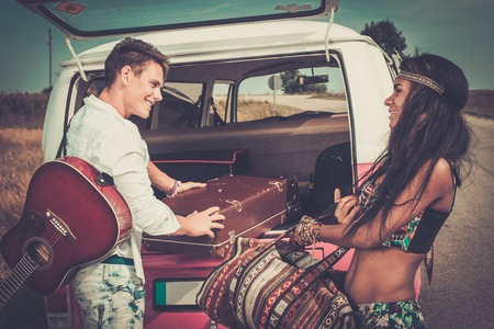 Multi-ethnic hippie couple with guitar packing luggage for a road trip photo