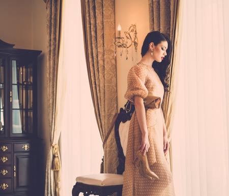 Beautiful young woman near window in luxury house interior  photo