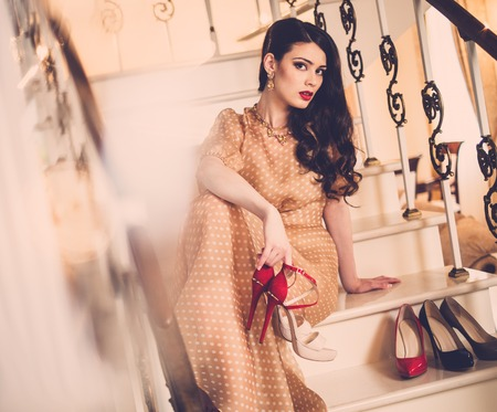 high heels shoes: Beautiful young lady sitting on a steps in luxury house interior  Stock Photo