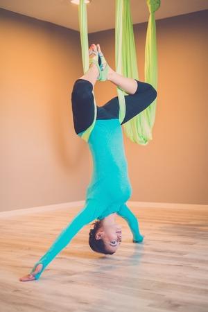 asanas: Young woman performing antigravity yoga exercise