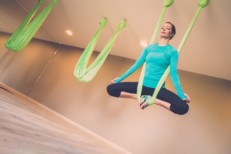 gravity: Young woman performing antigravity yoga exercise