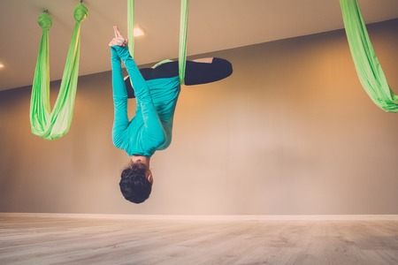 hang body: Young woman performing antigravity yoga exercise