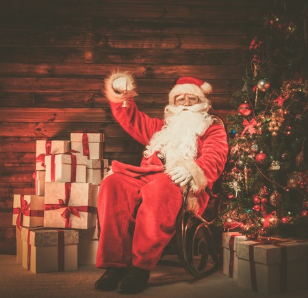 Santa Claus sitting on rocking chair in wooden home interior with little bell in his hand photo