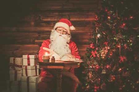 miracle tree: Santa Claus in wooden home interior sitting behind table and writing letters with quill pen Stock Photo