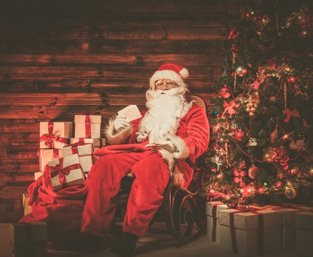 Santa Claus sitting on rocking chair in wooden home interior with letters in hands photo