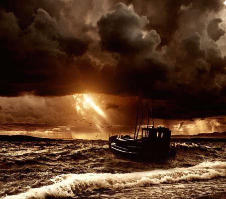 olas de mar: Barco de pesca en un mar tormentoso