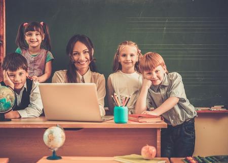 maestra preescolar: Grupo de compañeros felices con su profesor en clase cerca de la pizarra Foto de archivo
