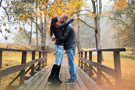 mid adult men: Happy middle-aged couple kissing outdoors on beautiful autumn day
