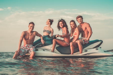 Group of multi ethnic friends sitting on a jet ski photo