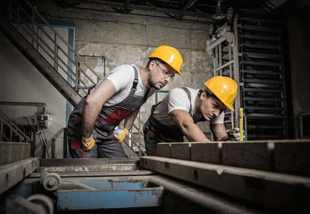 quality control: Worker and foreman in a safety hats performing quality check on a factory