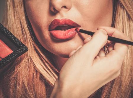 pomatum: Mua artist painting red lips with tassel Stock Photo