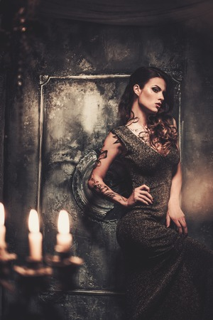 Tattooed beautiful woman in old spooky interior photo