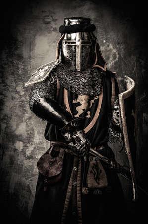 espadas medievales: Caballero medieval con una espada contra la pared de piedra