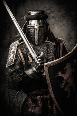 armour: Medieval knight with a sword against stone wall Stock Photo