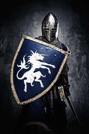 espadas medievales: Caballero medieval contra la pared de piedra Foto de archivo