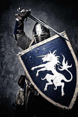 rycerz: Średniowieczny rycerz na tle kamiennego muru