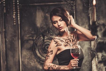 woman drinking wine: Tattooed beautiful woman in old spooky interior