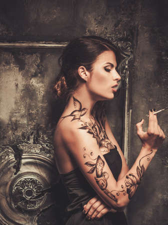 Smoking tattooed beautiful woman  in old spooky interior photo