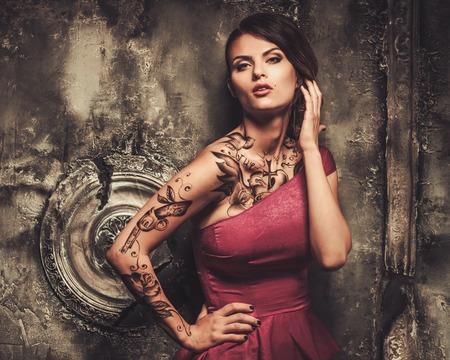 Tattooed beautiful woman in old spooky interior photo