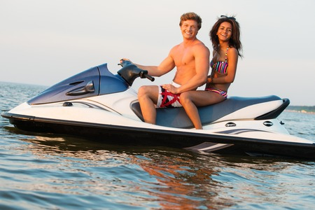moto acuatica: Multi étnica pareja sentada en una moto de agua