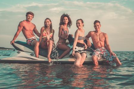 moto acuatica: Grupo de varios amigos ethnic que se sientan en un jet ski