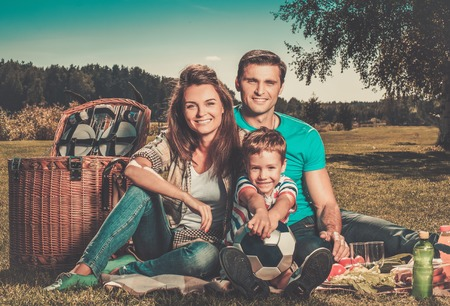 Young family having picnic outdoors  photo
