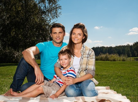 Young family with their child sitting on a blanket outdoors  photo