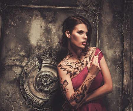 sexy girl smoking: Smoking tattooed beautiful woman  in old spooky interior