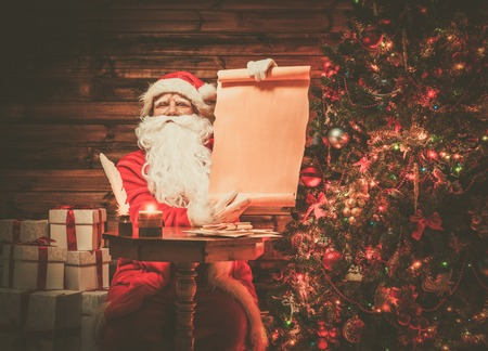 Santa Claus in wooden home interior holding blank wish list scroll photo