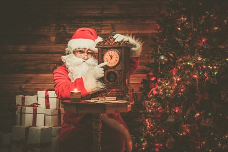 Santa Claus in wooden home interior showing time on a clock  photo