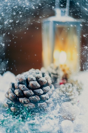 Christmas still life with cones and lantern on a snow  photo