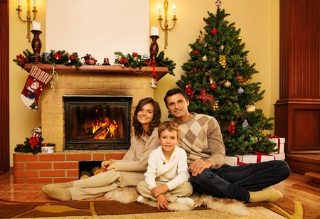 Family near fireplace in Christmas decorated house interior  photo