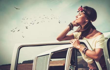 mujer hippie: Hippie de la muchacha en una minivan en un viaje por carretera