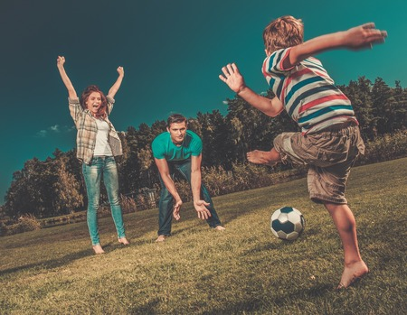 Happy young family playing football outdoors  photo